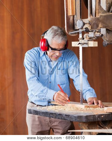 Senior carpenter marking on wood while cutting wood with bandsaw in workshop