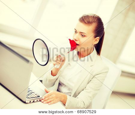 business concept - strict businesswoman shouting in megaphone in office