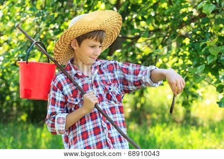 Boy in straw hat looking at caught fish