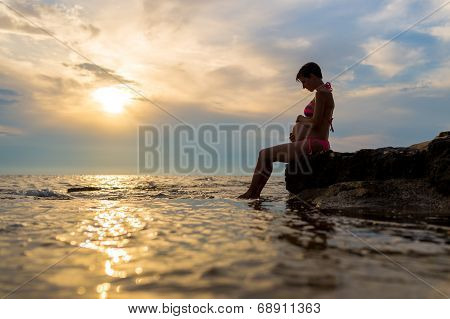 Pregnant Woman Sitting On A Rock By The Sea