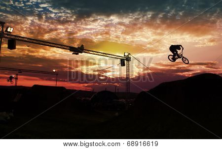 Silhouette of a man doing a jump with a bmx bike against sunset sky