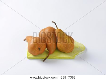 three ripe pears on the wooden cutting board