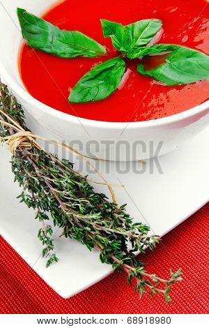 cold fresh diet tomato soup with basil thyme and dry pepper in big bowl over red mat on wood table ready to eat