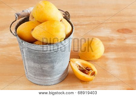 Loquat Fruit  In Bucket On Wooden Table