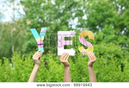 Hands holding up letters building word yes on natural background