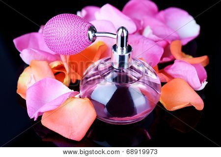 Perfume bottle with petals on black background