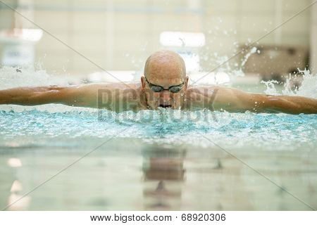 76 year old man swimming powerful butterfly stroke.