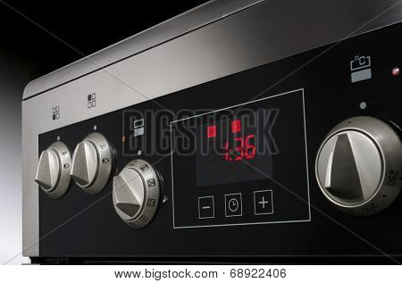 Close up of controls from a modern stainless steel oven with timer.