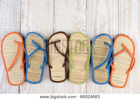 Mismatched Flip Flop sandals on a wooden deck. High angle shot of summer shoes.