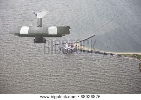 Old Airplane Flying Above Water And Lighthouse