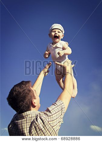 Father Tossing Baby In The Air