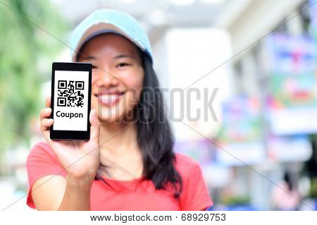 young asian woman hold smart phone show quick response coupon code on shopping street