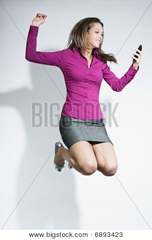 Businesswoman Jumping With Mobile Phone In Hands