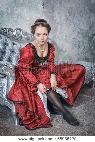Beautiful Woman In Medieval Dress Putting Stockings