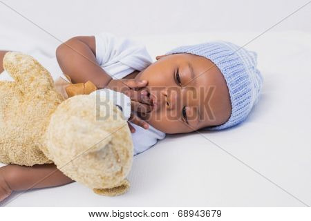 Adorable baby boy sleeping peacefully with teddy at home in the living room