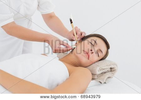 Close up of a beautiful young woman receiving ear candle treatment at spa center