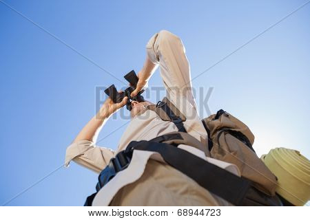 Hiker looking through binoculars on country trail on a sunny day