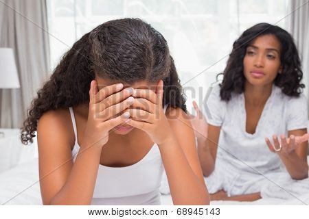Mother and daughter having an argument on bed at home in bedroom