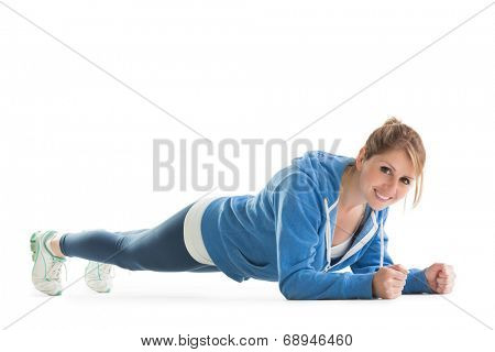 Smiling young woman in basic plank posture over white background
