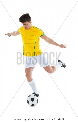 Football player in yellow jersey kicking ball on white background
