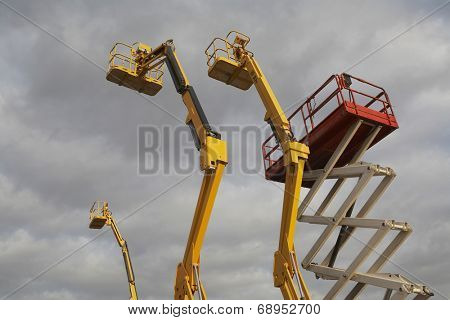 Hydraulic lift machines against stormy sky