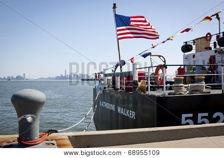 STATEN ISLAND, NY - MAY 25, 2014: The American flag flies from the stern of the USCGC Katherine Walker (WLM 552) moored at Sullivans Piers for Fleet Week NY with New York skyline in the background.