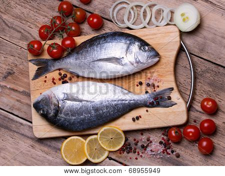 Two fresh gilt-head bream fish on cutting board with lemon, onion and tomato