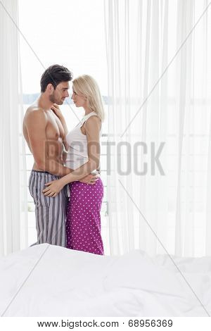 Side view of loving young couple embracing in hotel room