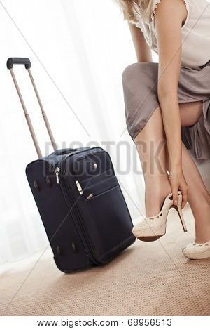 Low section of young businesswoman removing high heels in hotel room