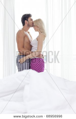 Side view of loving young man kissing woman on forehead in hotel room