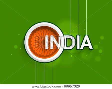 Stylish text INDIA with Asoka Wheel on shiny green background for Indian Independence Day celebrations.
