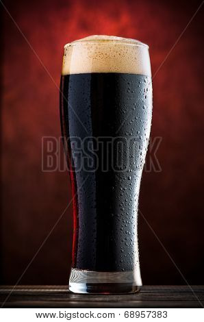 Glass Of Cold Dark Beer On Wooden Table