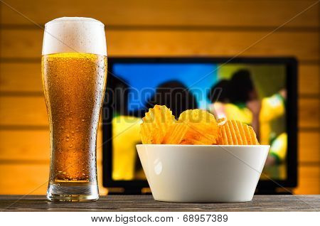Glass Of Cold Beer And Chips, Football Match In Background