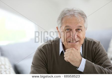 Portrait of smiling senior man sitting on sofa at home