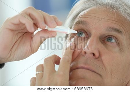 Senior man injecting eye serum