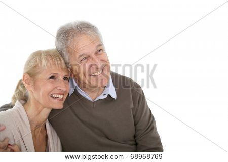 Senior couple looking on one side, being happy