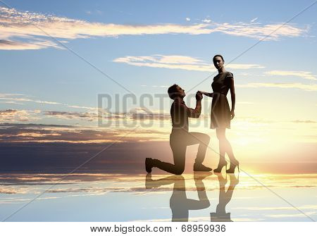 Silhouettes of man making proposal to woman