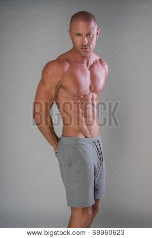 Handsome muscular man shirtless wearing grey pants