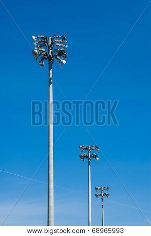 Row Of Stadium Flood Light Towers On Blue Sky.