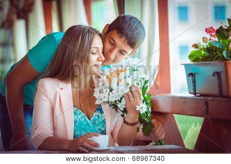 Proposal. Young couple in an open-air cafe