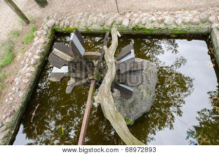 Stylized Water Mill On Stone Base Of Park Pond