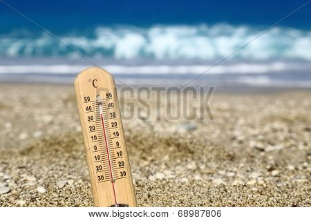 Thermometer on a beach shows high temperatures