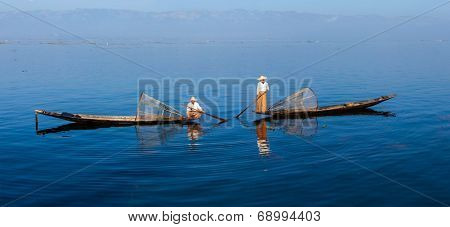 Panorama of traditional Burmese fishermen with fishing net at Inle lake in Myanmar famous for their distinctive one legged rowing style