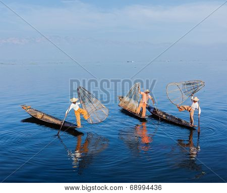 Myanmar travel attraction landmark - Traditional Burmese fishermen balancing with fishing net on boats at Inle lake in Myanmar famous for their distinctive one legged rowing style