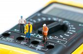 picture of ohm  - Miniature workers on top of multimeter - JPG