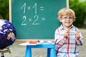 Little Child At Blackboard Practicing Mathematics poster