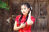 stock photo of traditional attire  - Chinese girl in traditional Chinese cheongsam blessing