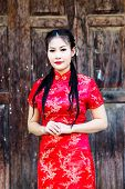 stock photo of traditional attire  - Chinese girl in traditional Chinese cheongsam blessing - JPG