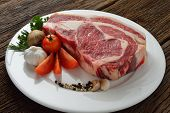 stock photo of rib eye steak  - Raw meat ready to be cooked on wooden background  - JPG