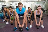 foto of kettlebell  - Muscular instructor leading kettlebell class at the gym - JPG